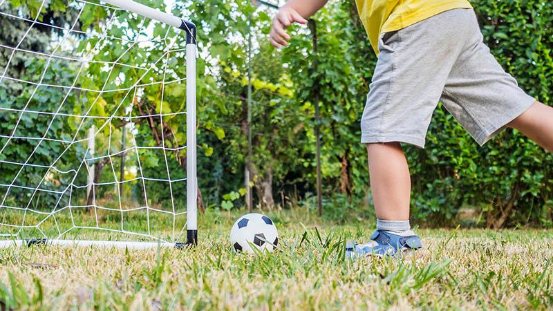 Chłopiec wkrótkich spodenkach kopie piłkę dobramki, naktórejrozciągnięto siatkę bramkarską