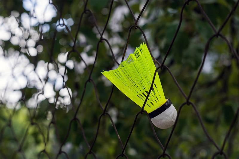 Jaskrawożółta, plastikowa lotka dobadmintona, którautknęłą woczkach siatki sportowej.