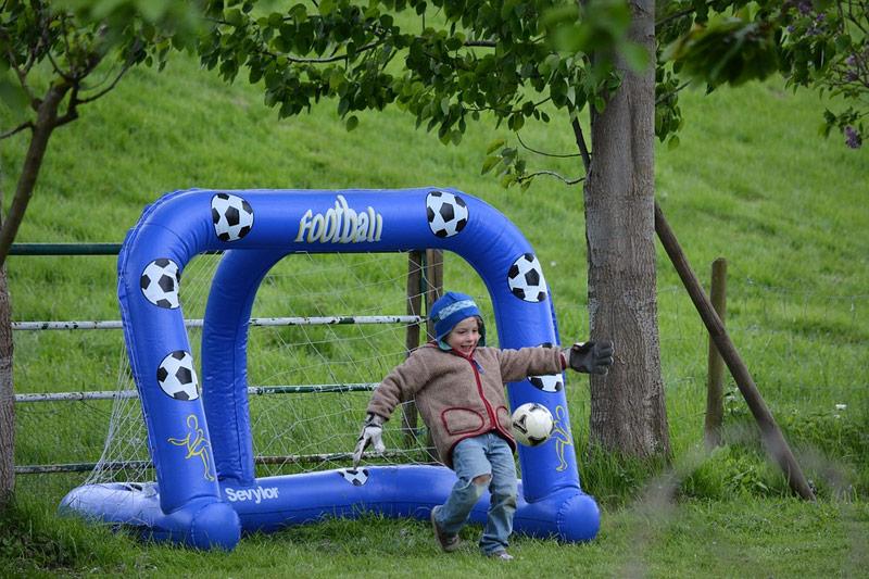 Uśmiechnięty chłopiec gra broni piłki przedwpadnięciem doniebieskiej bramki dopiłki nożnej dla dzieci.