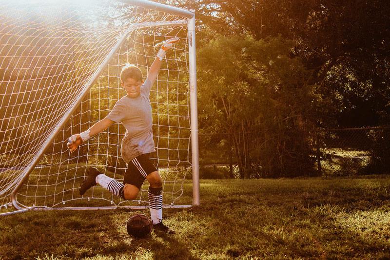 Chłopiec wykopujący piłkę wpadającą dobramki wogrodzie