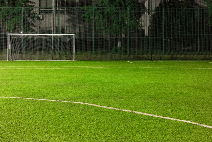 Boisko dopiłki nożnej otoczone wysoką, zieloną siatką napiłkochwyty