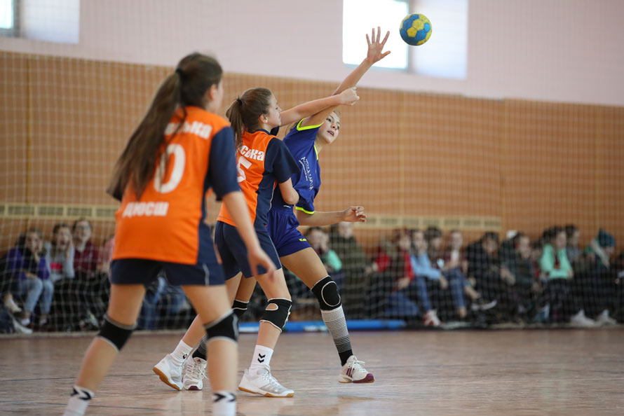Mecz piłki ręcznej na sali gimnastycznej osłoniętej piłkochwytem