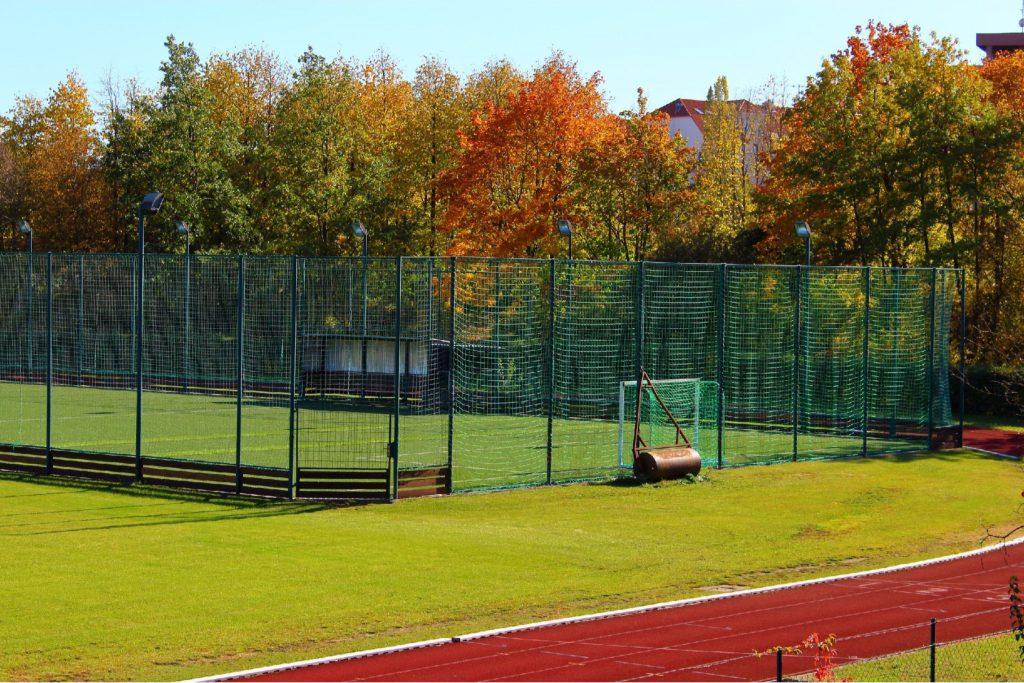 Podwyższone ogrodzenie z siatki na miejskim stadionie